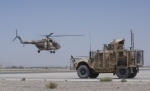 In this Tuesday, Aug. 18, 2015 photo, an Afghan National Army helicopter flies as a U.S. military vehicle passes, at Kandahar Air Base, Afghanistan.(AP Photo/Massoud Hossaini)