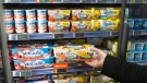 A man takes a yogurt pack from a refrigerator in a supermarket in Paris, Thursday, March 12, 2015. (AP / Michel Euler)