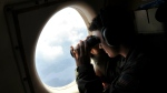 U.S. Navy LT. JG Dylon Porlas uses binoculars to look through the window of a U.S. Navy Lockheed P-3C Orion patrol aircraft searching the area in the Mediterranean Sea where the Egyptair flight 804 en route from Paris to Cairo went missing on May 19, in this photo taken on Sunday, May 22, 2016. (AP / Salvatore Cavalli)
