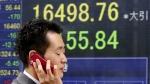 A man walks by an electronic stock board of a securities firm in Tokyo, Tuesday, May 24, 2016. (AP / Shuji Kajiyama)