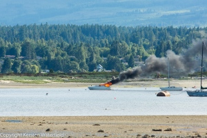 Flames are seen shooting from a sailboat in Comox Bay, Sun., May 29, 2016. (Courtesy Kersen Waterfield)