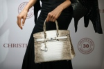 This file photo taken on May 04, 2016 shows Eunis Chan modelling a Matte White Himalaya Niloticus Crocodile Diamond Birkin with 18K gold and diamond hardware -- one of the most valuable handbags in the world -- during a preview at Christie's in Hong Kong. (© AFP PHOTO/ISAAC LAWRENCE)