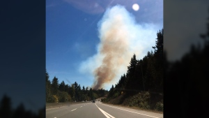 A plume of smoke is seen in the distance as a wildfire burned in Mill Bay, Aug. 25, 2016. (Twitter/@edoc89)