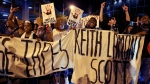 Protesters shout as they march in the streets of Charlotte, N.C. Friday, Sept. 23, 2016, to protest Tuesday's fatal police shooting of Keith Lamont Scott. (AP Photo / Chuck Burton)