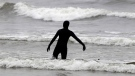 A surfer walks into the surf at Indian Beach, in Ecola State Park, near Cannon Beach, Ore., on July 30, 2010. (Rick Bowmer / AP)