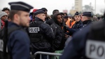 Police officers control a queue of migrants waiting to register at a processing centre in 'the jungle' near Calais, France,on Oct. 24, 2016. (Emilio Morenatti / AP)