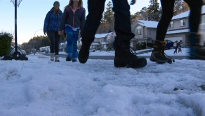Children walk on an icy sidewalk in Nanaimo after a substantial snowfall earlier in the week. Dec. 7, 2016. (CTV Vancouver Island)