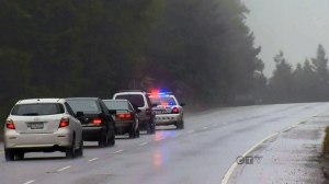 A police car leads cars around the scene of a collision along the Malahat Highway near Victoria, Sunday, Oct. 14, 2012. (CTV BC)